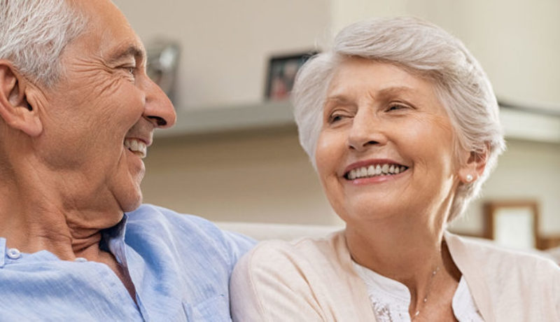 Elderly married couple smiling and discussing the best skilled nursing facilities.