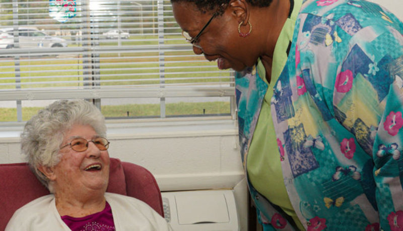 Nurse interacting with patient at skilled nursing facility.